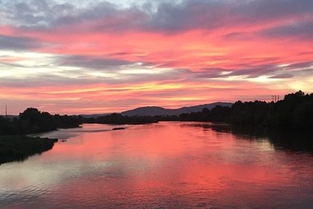 a beautiful pink and purple sunset reflecting over a river